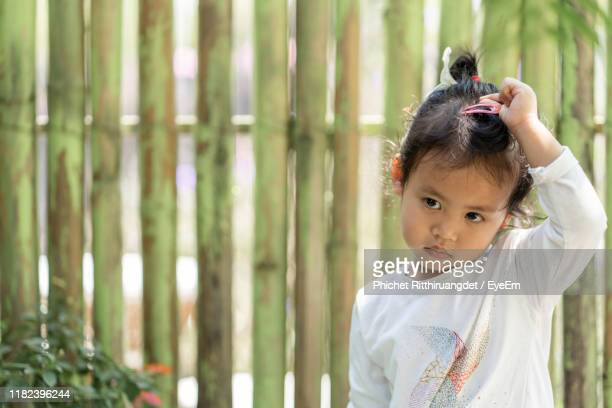 girl standing outdoors - phichet ritthiruangdet stock photos and pictures