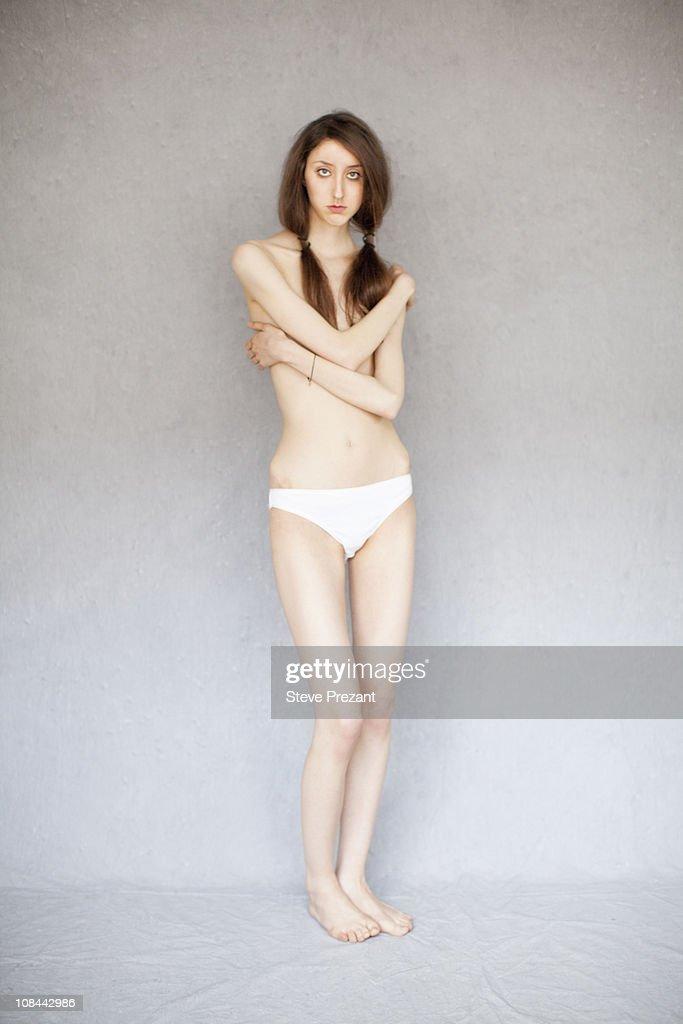 Slim naked girl wrapped by rope posing in studio — Stock