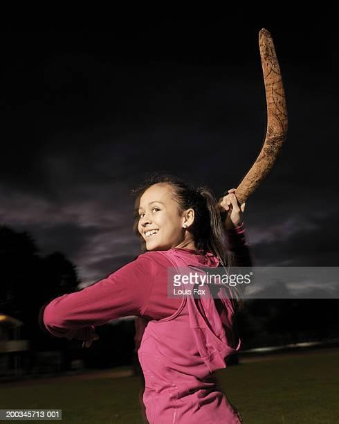 Girl (10-12) standing throwing boomerang, smiling