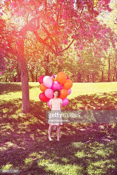 Niña de pie bajo un árbol con globos aerostáticos blossomming ramo.