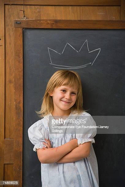 "girl (6-7) standing under crown drawn on blackboard, smiling - ""compassionate eye"" fotografías e imágenes de stock"