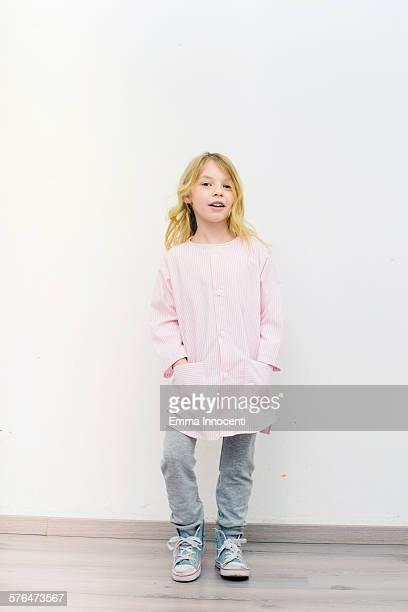 girl standing wearing nursery school apron