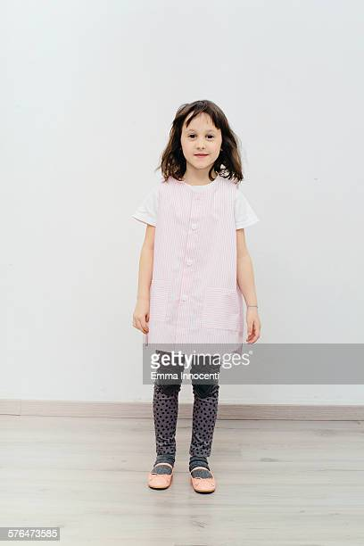 girl standing wearing pink nursery school apron
