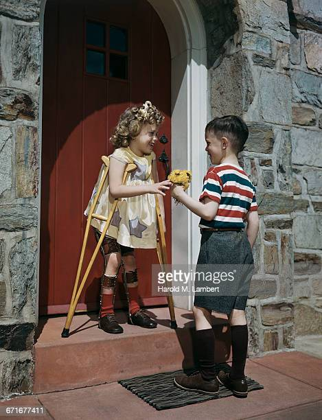 Girl Standing With Crutches And Receiving Flowers From Boy