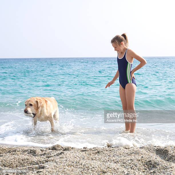 Girl (10-11) standing with dog at water's edge on beach