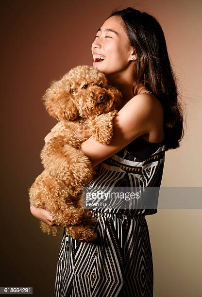 Girl standing with dog in arms happily