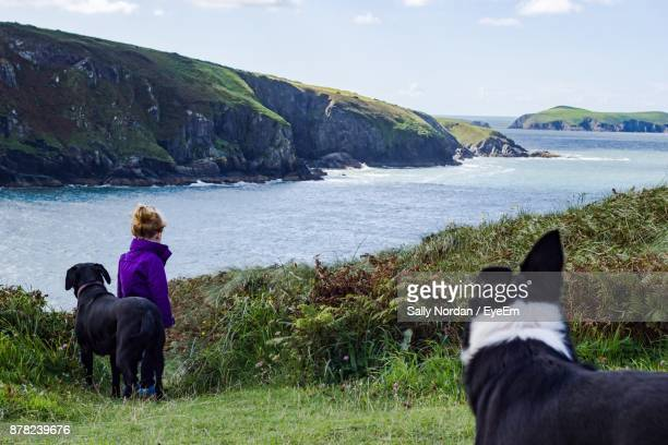 Girl Standing With Dogs On Grassy Field Against Sea