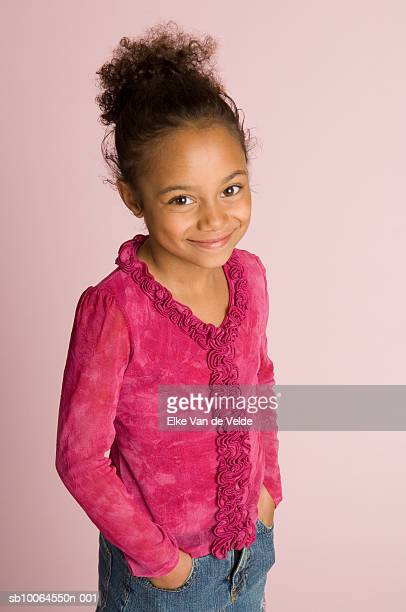 girl (6-7 years) standing with hands in pockets, portrait, elevated view, studio shot - 6 7 years stock pictures, royalty-free photos & images