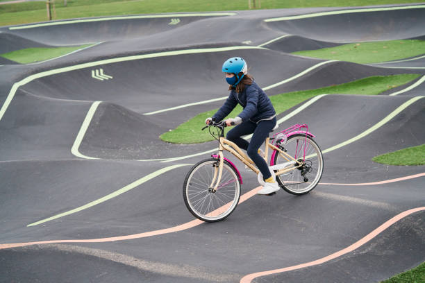 Girl standing with her bike on a concrete pumptrack.