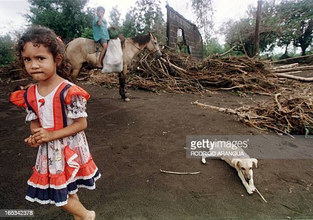 A girl stands 05 November in Posoltega Nicaragua in front of damages caused by a mudslide from Hurricane Mitch Posoltega is 135 kilometers north east...