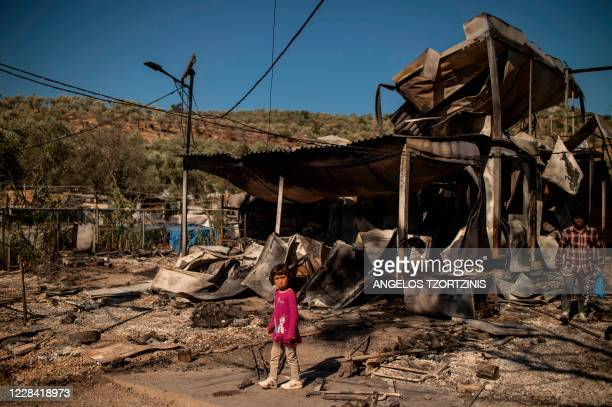 Girl stands amid rubbles in the burnt camp of Moria on the island of Lesbos after a major fire broke out, on September 9, 2020. - Thousands of asylum...