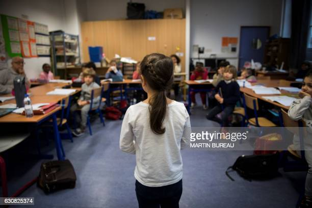 A girl stands as pupils following the Freinet teaching method study in a class room on December 12 2016 in Paris The Freinet teaching method...