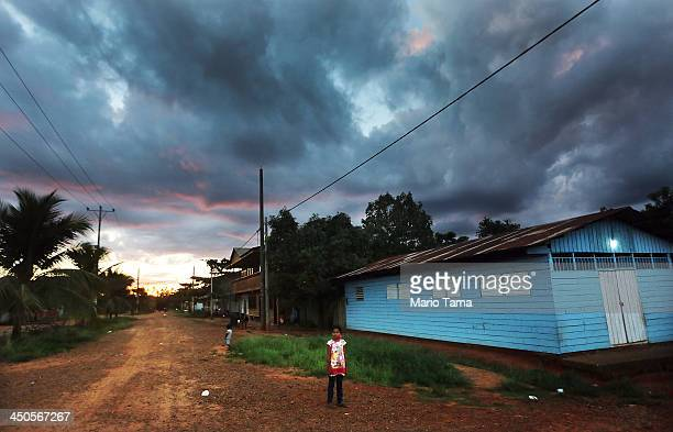 A girl stands at sunset in a deforested section along the Interoceanic Highway in the Amazon lowlands on November 18 2013 in Planchon Madre de Dios...