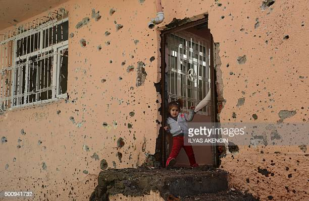 TOPSHOT A girl stands at the entrance of a damaged house in the Sur district in Diyarbakir on December 11 2015 A policeman was killed on December 9...