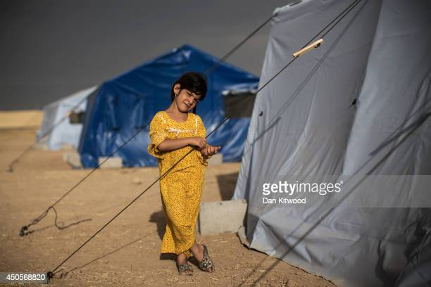 A girl stands beside her tent at a temporary displacement camp set up next to a Kurdish checkpoint on June 13 2014 in Kalak Iraq Thousands of people...