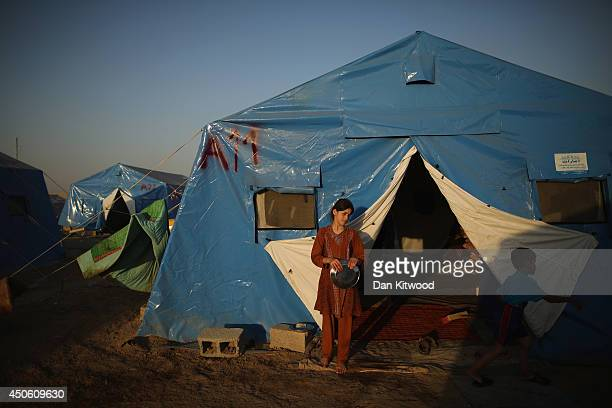 A girl stands besides her tent at a temporary displacement camp set up next to a Kurdish checkpoint on June 14 2014 in Kalak Iraq Thousands of people...