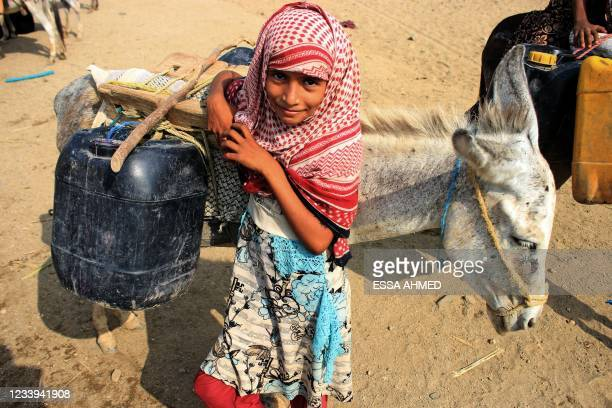 Girl stands by a donkey carrying jerrycans of water filled from a cistern at a make-shift camp for the internally displaced in Yemen's northern...