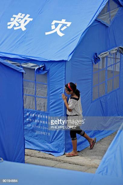 A girl stands by a tent in a refugee camp near the border separating China and Myanmar in the Chinese border town of Nansan on August 31 2009 around...