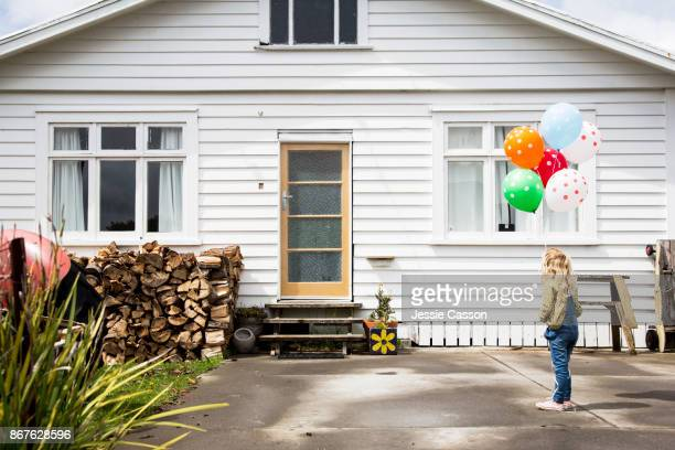 Girl stands in front of a bungalow holding colourful balloons