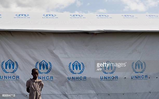 A girl stands in front of a tent with the logos of the UN refugee agency at a camp for Internally Displaced People in Mugunga on November 4 2008...