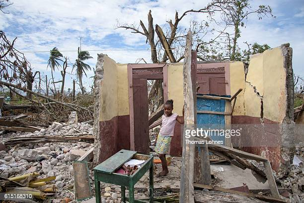 A girl stands in here destroyed house on October 14 2016 in a small village near Les Cayes Haiti Matthew had heavily devastated the southern half of...