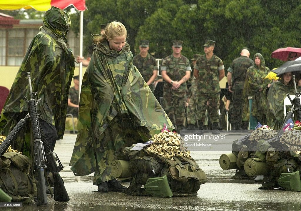 girl stands in the falling rain before a soldier s possesions before