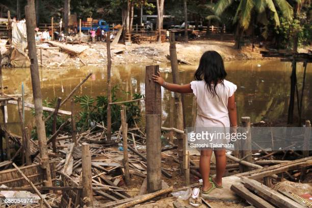 A girl stands in the ruins of her own house which was demolished by an administrative order due to land development