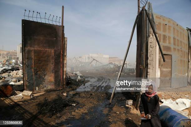 Girl stands near the wreckage of a store of vehicle oil and tyres targeted by airstrikes carried out by the Saudi-led coalition on July 02, 2020 in...