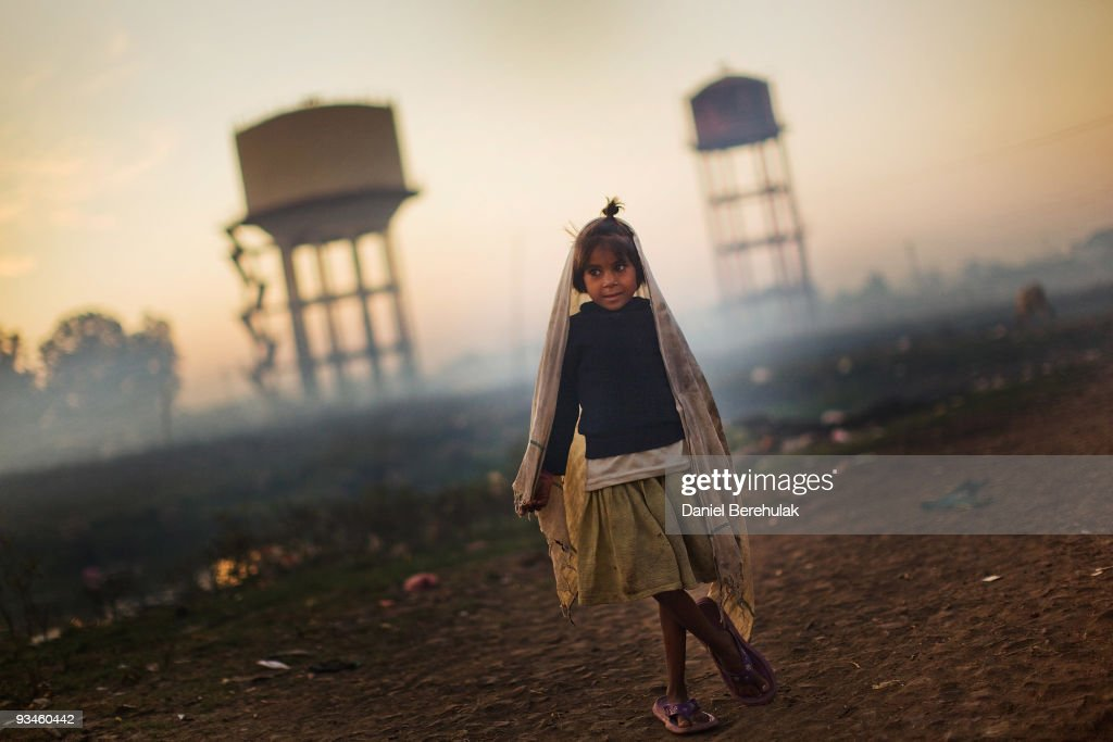 A girl stands near water towers outside her home near the site of the Union Carbide factory on November 27, 2009 in Bhopal, India. Twenty-five years after an explosion causing a mass gas leak, in the Union Carbide factory in Bhopal, killed at least eight thousand people, toxic material from the biggest industrial disaster in history continues to affect Bhopalis. A new generation is growing up sick, disabled and struggling for justice. The effects of the disaster on the health of generations to come, both through genetics, transferred from gas victims to their children and through the ongoing severe contamination, caused by the Union Carbide factory, has only started to develop visible forms recently. Annan suffers from cerebral palsy and receives vital rehabilitative support and care at the Chingari Trust Rehabilitation Clinic.