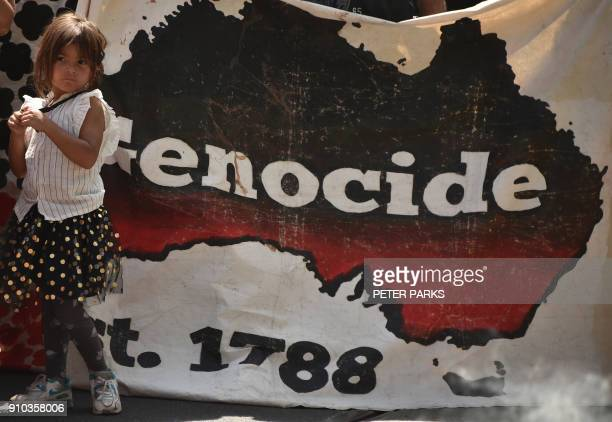 A girl stands next to a banner during an 'Invasion Day' rally on Australia Day in Melbourne on January 26 2018 Thousands of supporters joined rallies...