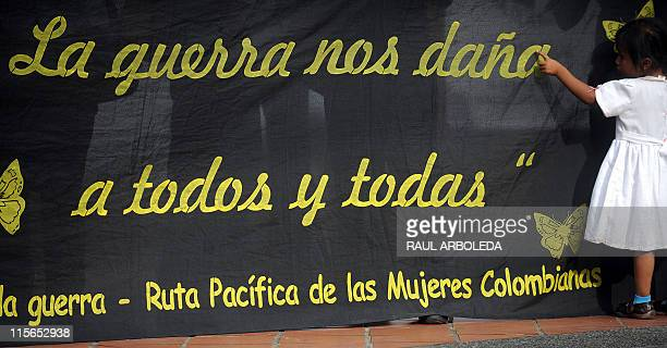A girl stands next to a banner reading 'War hurts us all' during a protest against the killing of Ana Fabricia Cordoba Cabrera on June 8 in Medellin...
