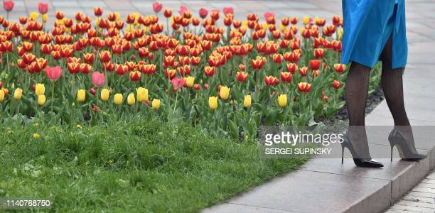 Girl stands next to a flower bed with tulips in the center of Kiev during a spring sunny day on May 2, 2019.