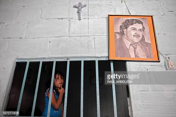 A girl stands next to a portrait of Colombian drug lord Pablo Escobar inside her house at Pablo Escobar neighborhood on December 1 2010 in Medellin...