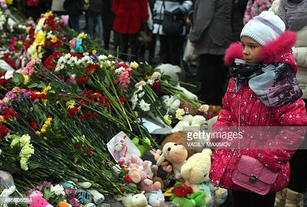 A girl stands next to flowers at a makeshift memorial for the victims of the Russian MetroJet Airbus A321 crash on November 4 2015 in Saint...