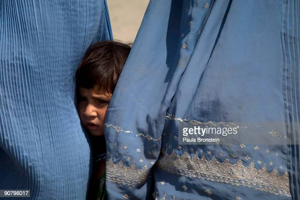 A girl stands next to her mother waiting in line with Afghan widows to receive their food rations from CARE international relief agency on the second...
