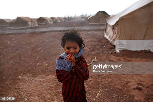 A girl stands next to her tent as wind and rain pound the massive tent city June 2 2009 at Jalozai camp 15km from Peshawar Pakistan According to the...