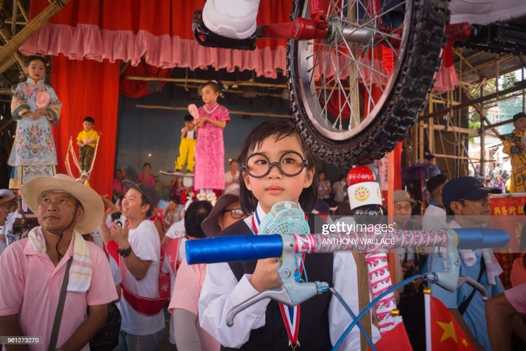 A girl stands on a float while dressed in character as world number one female snooker player Ng On Yee, who she will portray during the annual Cheung Chau bun festival parade in Hong Kong on May 2...