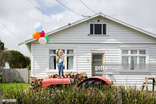 Girl stands on a tractor holding colourful balloons in front of a bungalow