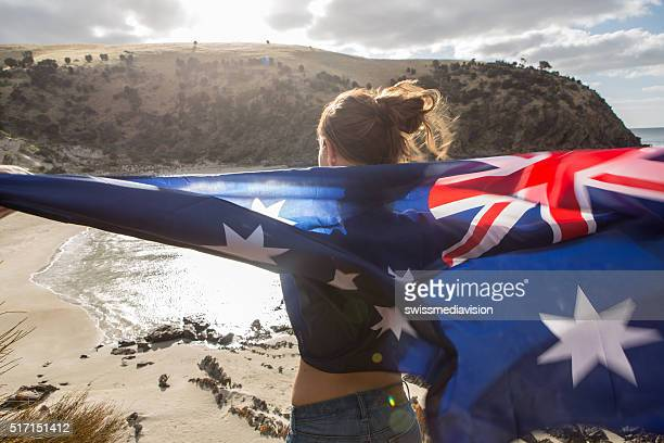 Girl stands on cliff above beach holding Australian's flag