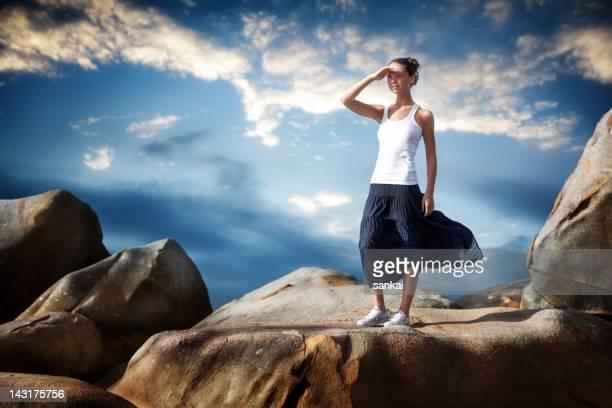 jeune fille se dresse sur d'énormes rochers et stares dans la distance - jupe vent photos et images de collection