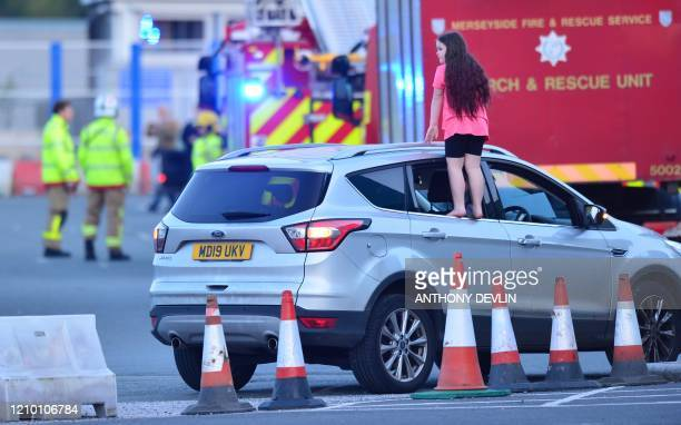 A girl stands on the edge of a car window to get a better view ahead of a national clap for carers to show thanks for the work of Britain's National...