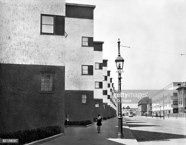 A girl stands on the sidewalk near a lamppost amid rows of apartment buildings FrankfurtamMain Germany 1928