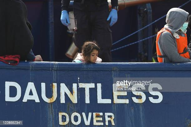 A girl stands onboard the DHB Dauntless tug boat as a group of migrants are brought to shore by the UK Border Force after illegally crossing the...