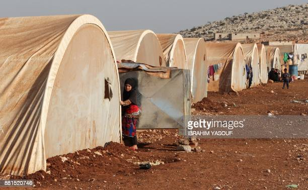 A girl stands outside a tent at the Furat camp for the displaced from Deir Ezzor north of the town of Kafr Dariyan in the countryside of the northern...