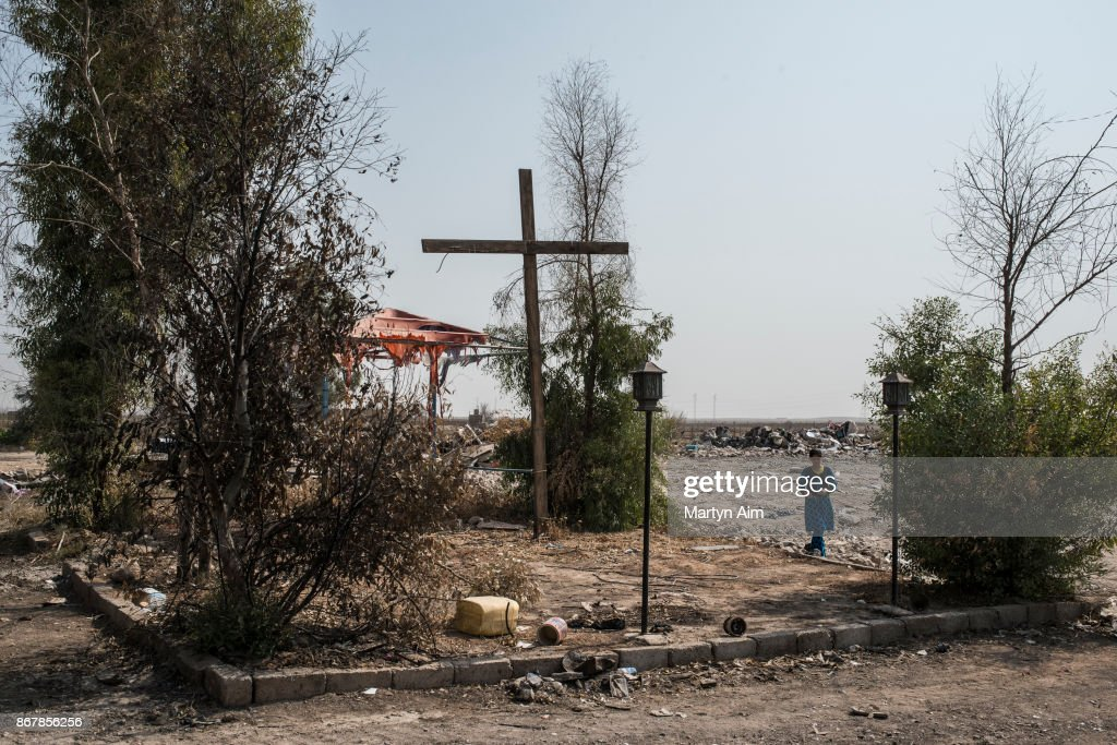 A girl stands under a wooden cross in the recently resettled Catholic town of Karemles, Iraq, on September 8, 2017.