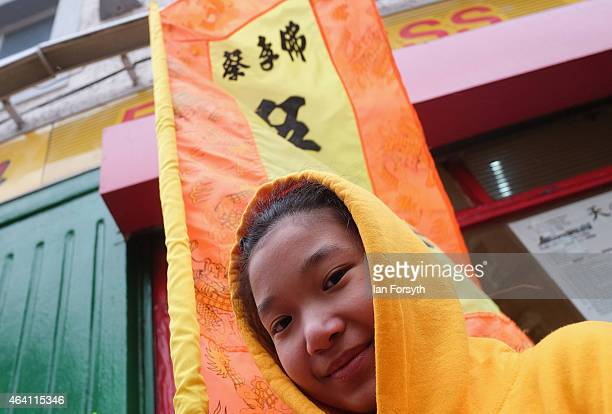 A girl stands with a flag during a Dragon dance performance as the Chinese community come together to welcome in the Chinese New Year on February 22...