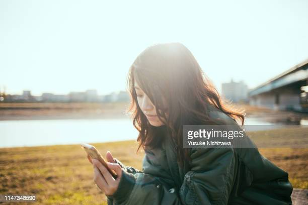 girl staring at a smartphone - yusuke nishizawa photos et images de collection