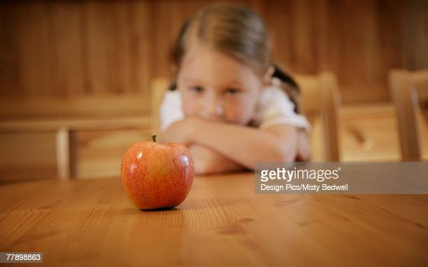 Girl staring at an apple