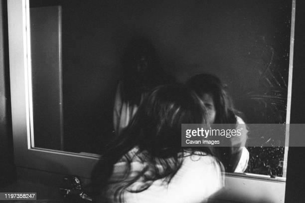 girl staring closely into mirror with creepy ghost girl in reflection - goose bumps stock pictures, royalty-free photos & images