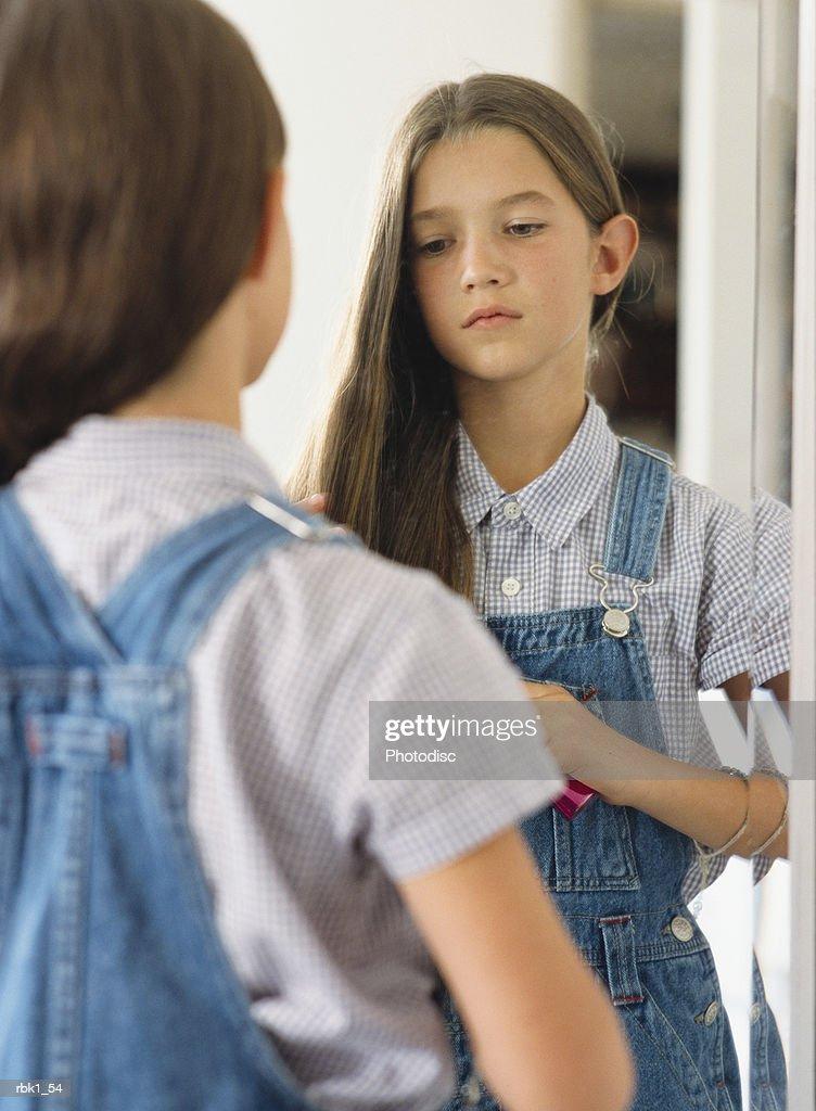 Girl (10-12) staring into mirror, brushing hair : Stockfoto